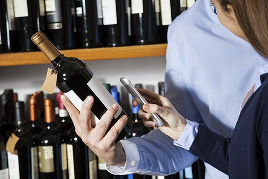 Wine and spirit store associate using a smartphone to scan a wine bottle label to show a customer a digital promotional offer