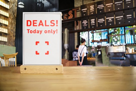 Custom in-store signage promoting exclusive deals that was printed onsite, sitting on the counter of a coffee shop