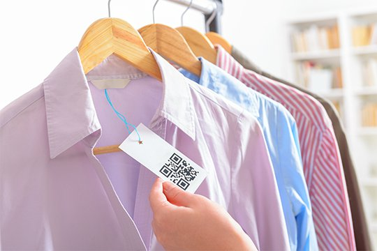 Customer holding a price tag with a QR code hanging from a men's dress shirt in a retail store