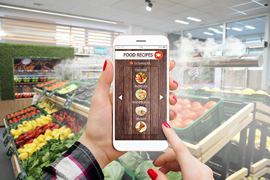 Female customer using an augmented reality app on their smartphone to get recipe ideas in the produce section of a grocery store