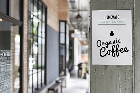 Custom printed retail poster advertising organic coffee hanging on the side of an interior vertical wood plank wall