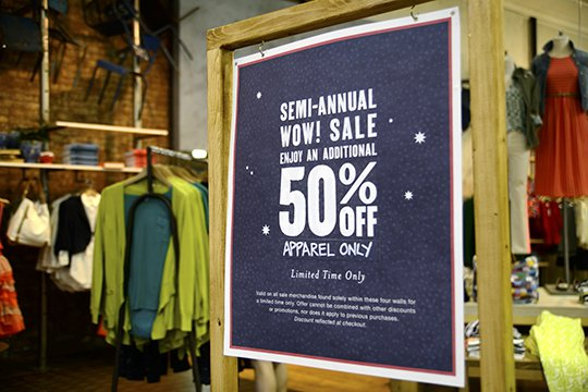 In-store retail signage printed with OKI Connected Print advertising a 50% off semi-annual sale on women's apparel