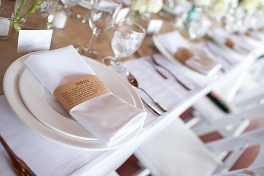 Custom printed menu on a paper napkin ring for a table setting for a large, reception dinner